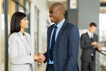 Indian woman shakes hands with African American man in business setting.
