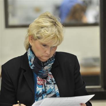 A woman (Rita) works at a desk with paperwork.